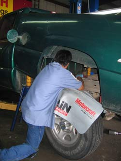 The technician is replacing the faulty electric fuel pump assembly inside the fuel tank.