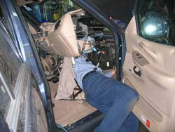 A technician unbolting the inner air conditioning / heater core plenum assembly to access and replace a broken blend door assembly on a 1999 Ford Expedition.